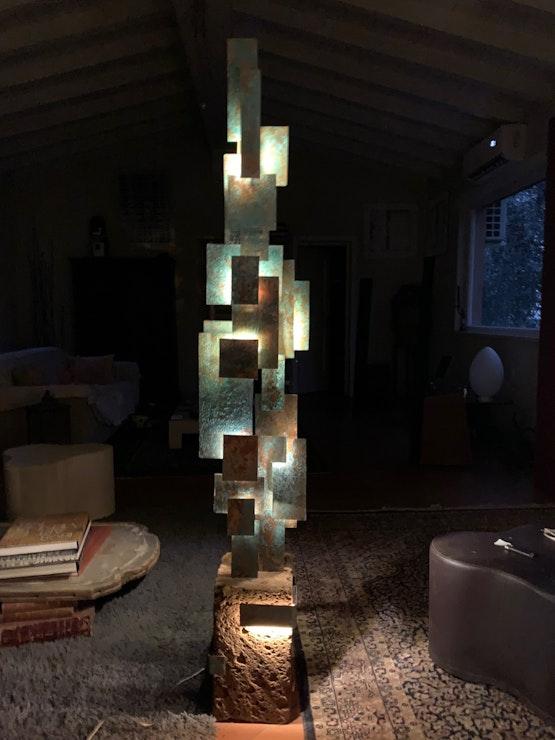 Escultura luminosa grande con rectángulos de acero (con lámina de cobre oxidada) sobre una base de toba