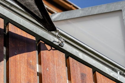 Primer plano de un imán con mosquetón integrado que sujeta un toldo vela a la barandilla de un balcón.