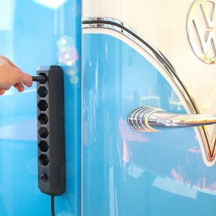 Steckdosenleiste hängt dank Magneten an einem Kühlschrank