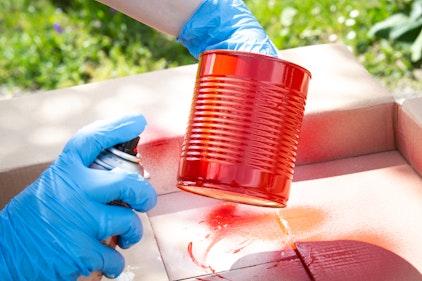 Conservenblik wordt met rode spuitlak bespoten