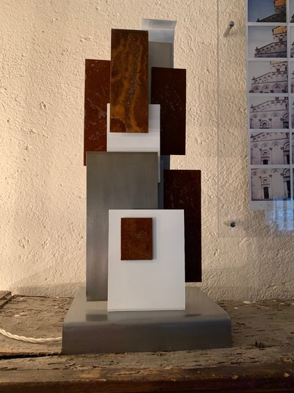 Small light sculpture with steel rectangles and steel base