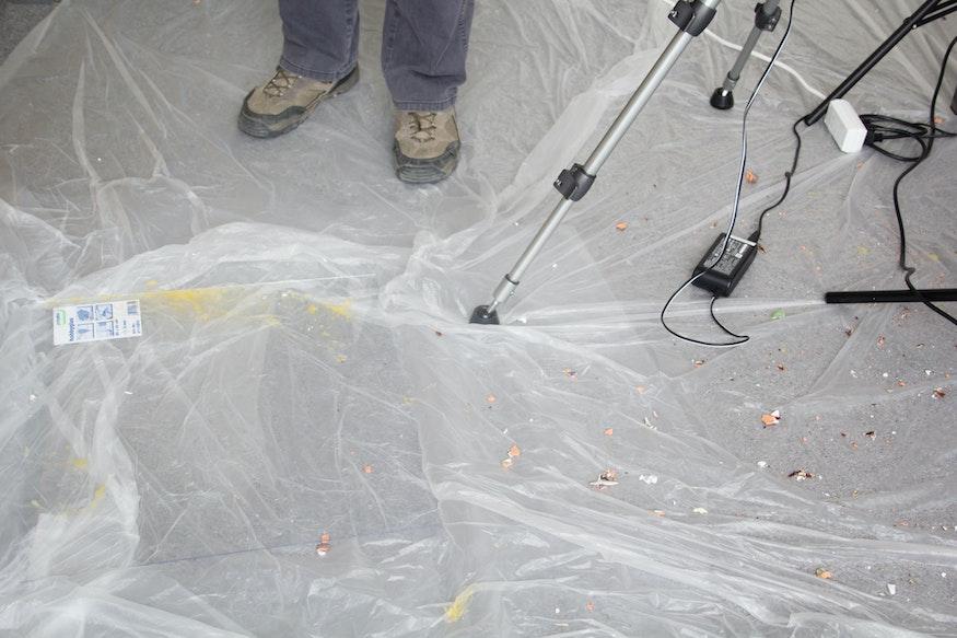 Spetters eigeel op de vloer, schoenen en equipment.