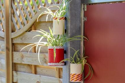 Zwevende bloempotten: Dankzij magneten blijven de conservenblikken aan metalen strips op het terras vastzitten